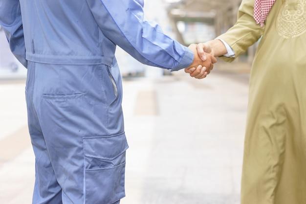 Il meccanico sta stringendo la mano al cliente arabo. Foto Premium
