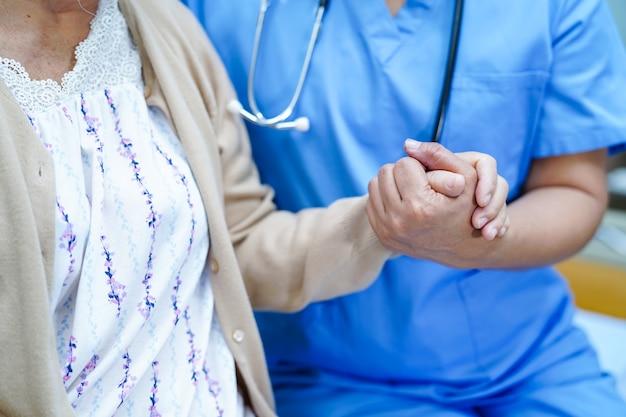 Il medico asiatico del fisioterapista dell'infermiere cura, aiuta e sostiene la donna anziana o anziana della signora anziana Foto Premium