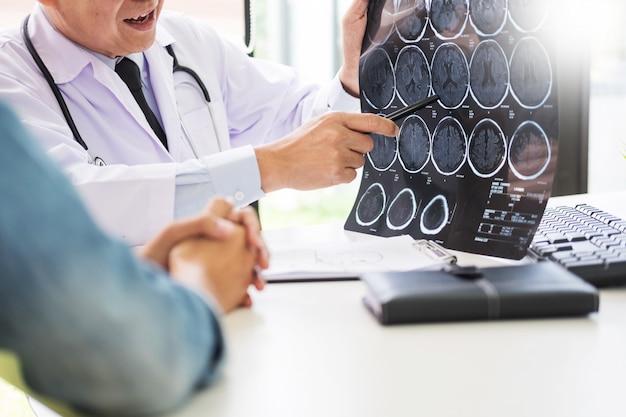 Il medico che analizza una scansione o un film a raggi x spiega una scansione tc che parla al cervello del paziente Foto Premium