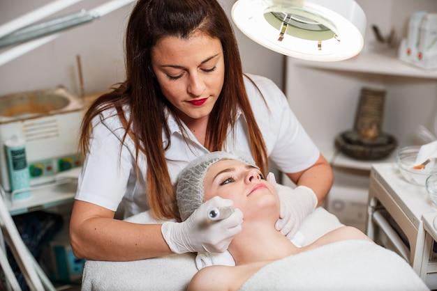 Il medico-cosmetologo esegue una procedura di pulizia ad ultrasuoni della pelle del viso Foto Premium
