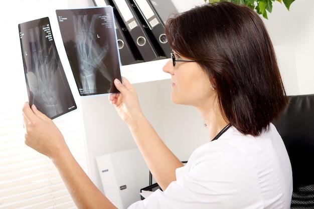 Il medico della giovane donna sta esaminando i raggi x Foto Gratuite