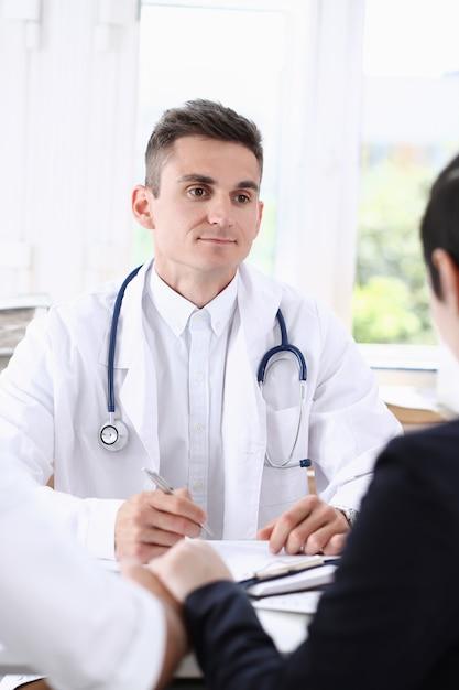 Il medico di famiglia maschio ascolta attentamente i giovani Foto Premium