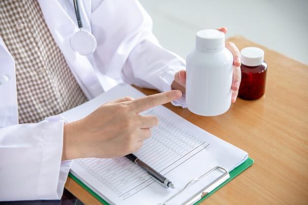Il medico indicò il dito per introdurre la bottiglia di medicina al paziente. Foto Premium