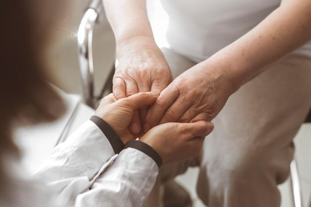 Il medico tiene la mano di una donna anziana Foto Premium