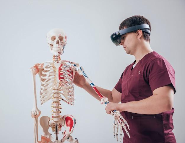 Il medico usa occhiali di realtà aumentata per esaminare lo scheletro umano Foto Premium