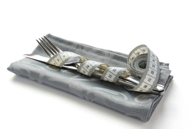 Il metro a nastro avvolto intorno al coltello e forchetta su bianco Foto Premium