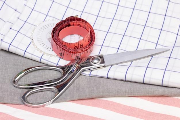 Il metro a nastro e le forbici sono su un tessuto di cotone. concetto di cucito, cucito con tessuti naturali. Foto Premium