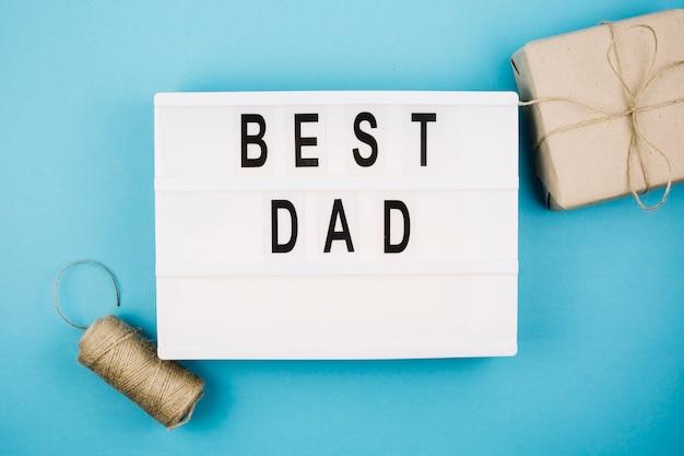 Il miglior titolo di papà sul tablet vicino al contenitore e al filo presenti Foto Gratuite