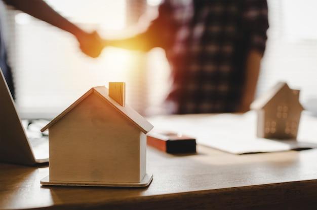 Il modello della casa di legno sullo scrittorio del posto di lavoro con le mani del gruppo del muratore che stringono il saluto inizia sul nuovo contratto di progetto di piano Foto Premium