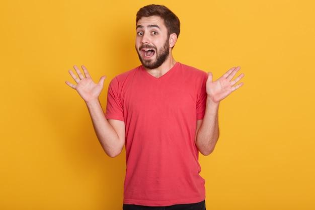 Il modello maschio barbuto caucasico scosso e confuso veste l'attrezzatura casuale che sta con le palme spante e la bocca aperta Foto Gratuite