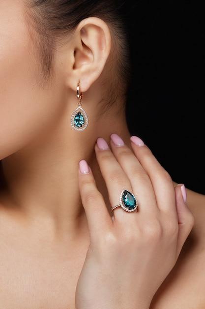 Il modello mostra orecchini e anello con bellissime pietre preziose blu Foto Gratuite