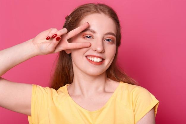 Il modello positivo sorridente posa isolato su sfondo rosa brillante in studio con la mano di vittoria vicino al suo occhio destro, indossando maglietta gialla Foto Gratuite