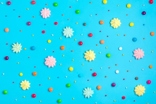 Il modello senza cuciture dei dolci variopinti della miscela - la lecca-lecca, la meringa, il cioccolato, dolce spruzza su fondo blu Foto Premium