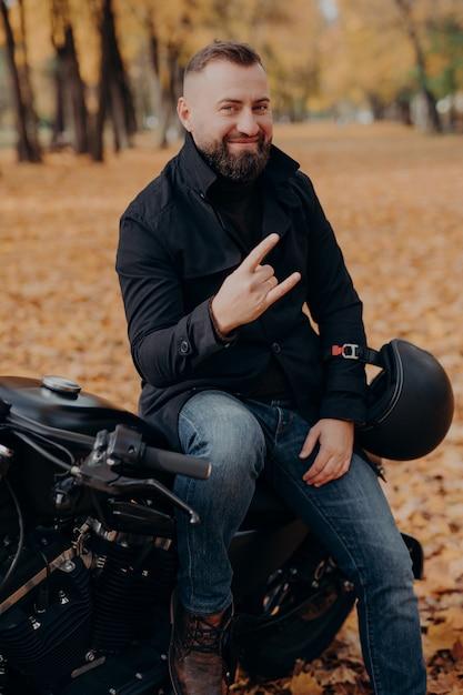 Il motociclista maschio barbuto bello fa il gesto del corno con le dita, si sente fresco, indossa cappotto e jeans neri, si siede su una moto veloce Foto Premium