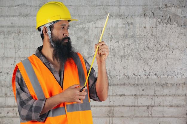 Il muratore è la misura di nastro e sta pensando al piano sul cantiere. Foto Gratuite