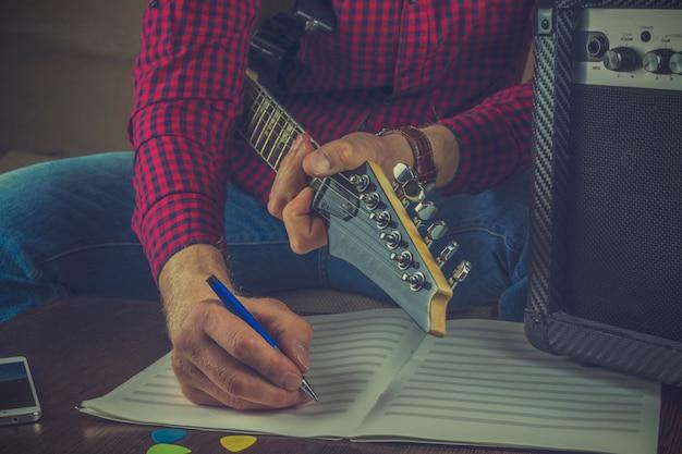 Il musicista dei pantaloni a vita bassa si siede sul divano con una chitarra elettrica e registra le note della sua melodia Foto Premium