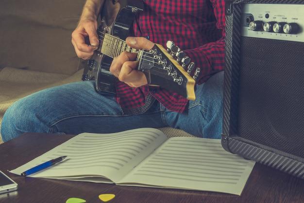 Il musicista si siede sul divano e suona la chitarra elettrica. prima di lui le note e una guita Foto Premium