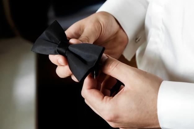 Il muzhchin, una camicia bianca con pantaloni grandi e scuri alla moda, regge un bowknot a farfalla Foto Premium