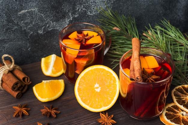Il natale ha sciupato il vino rosso con le spezie e la frutta su una tavola rustica di legno Foto Premium