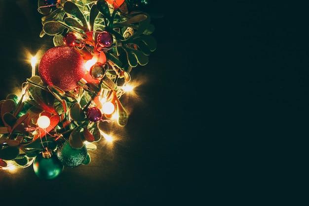 Il natale si avvolge con luce decorativa su fondo di legno scuro Foto Premium