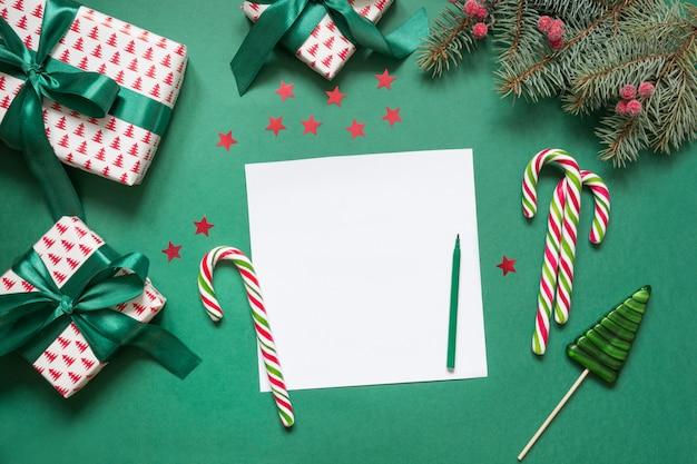 Il natale svuota la lettera in bianco a santa o l'invito su verde. vista dall'alto. Foto Premium