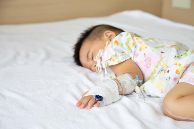 Il neonato asiatico che dorme sul letto con l'infusione ha messo al dipartimento del bambino nell'ospedale Foto Premium