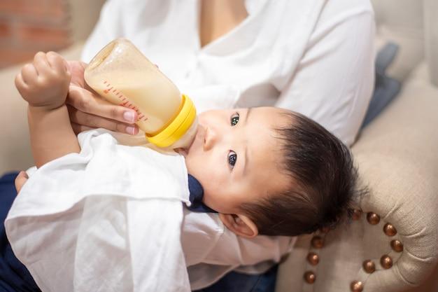 Il neonato sveglio sta bevendo il latte dalla bottiglia dalla mamma Foto Premium