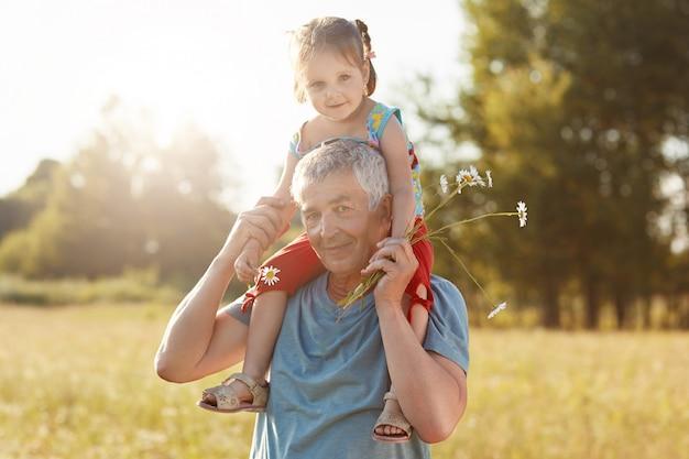 Il nonno e la nipote felici si divertono insieme all'aperto. maschio dai capelli grigi dare cavalluccio per bambino piccolo Foto Gratuite