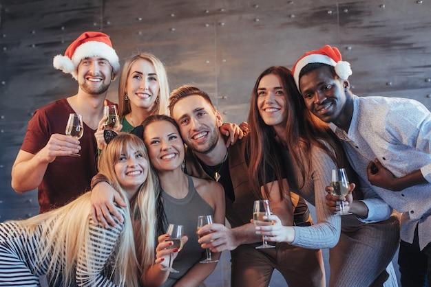 Il nuovo anno sta arrivando! gruppo di giovani multietnici allegri in cappelli di santa sul partito, posando concetto emozionale della gente di stile di vita Foto Premium
