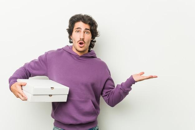 Il pacchetto delle pizze della tenuta del giovane ha impressionato lo spazio della copia della tenuta sulla palma. Foto Premium