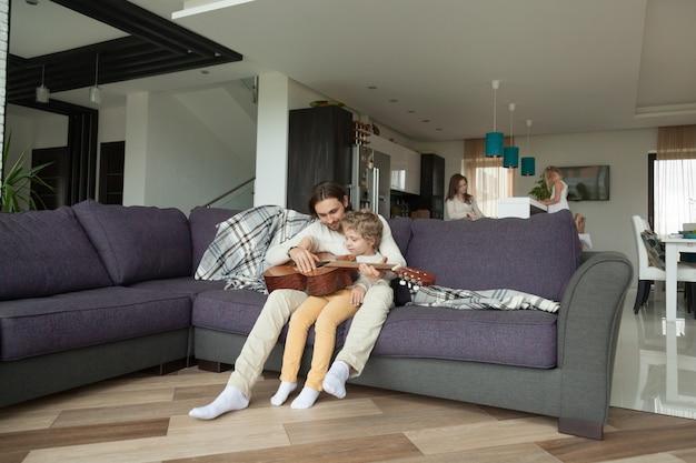 Il padre d'istruzione del padre gioca la chitarra, madre d'aiuto della figlia sulla cucina Foto Gratuite