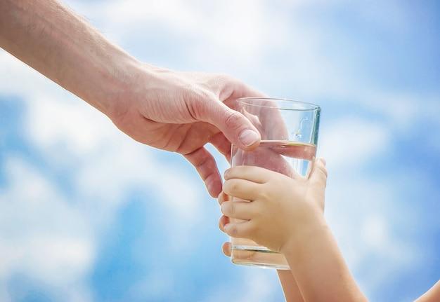 Il padre dà al bambino un bicchiere d'acqua. messa a fuoco selettiva Foto Premium