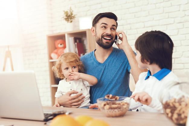Il padre è impegnato a crescere i figli mentre lavora Foto Premium