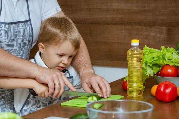 Il padre ed il figlio di vista frontale in cucina hanno tagliato le verdure per insalata. Foto Premium