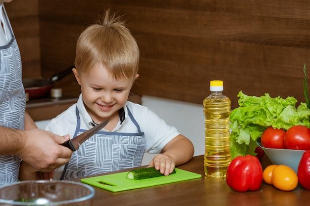 Il padre ed il figlio di vista frontale in cucina hanno tagliato le verdure per insalata Foto Premium