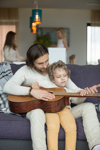 Il papà che insegna al piccolo figlio gioca la chitarra, figlia che cucina aiutando la madre Foto Gratuite