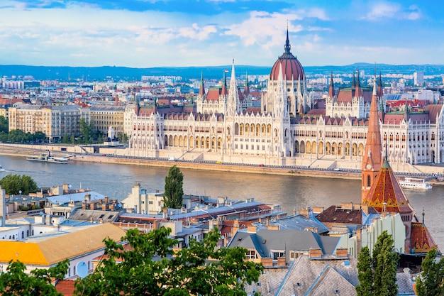 Il parlamento e la riva del fiume a budapest in ungheria durante la bella giornata di sole estivo contro il cielo blu e nuvole. Foto Premium