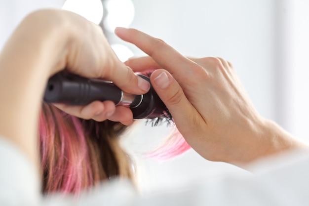 Il parrucchiere fa lo stile di capelli della donna Foto Premium