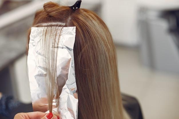 Il parrucchiere ha colorato i capelli il suo cliente in un parrucchiere Foto Gratuite