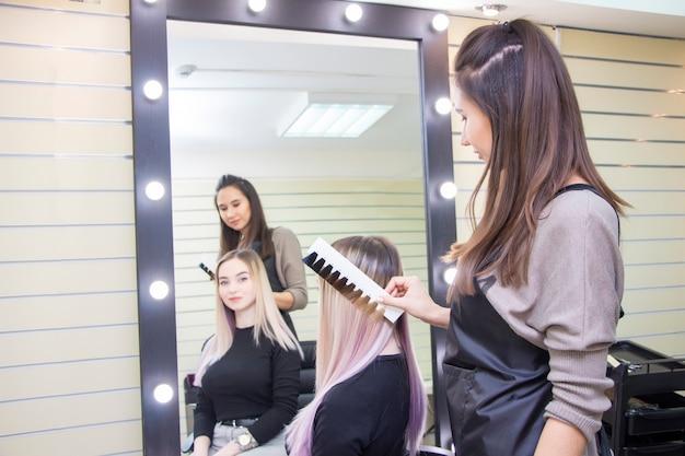 Il parrucchiere seleziona il colore dei capelli sulla tavolozza del catalogo. colorazione dei capelli per una ragazza in un salone di bellezza. Foto Premium