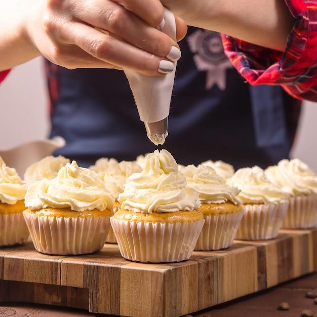 Il pasticcere femminile in grembiule blu e una camicia scozzese rossa applica la crema ai cupcakes Foto Premium