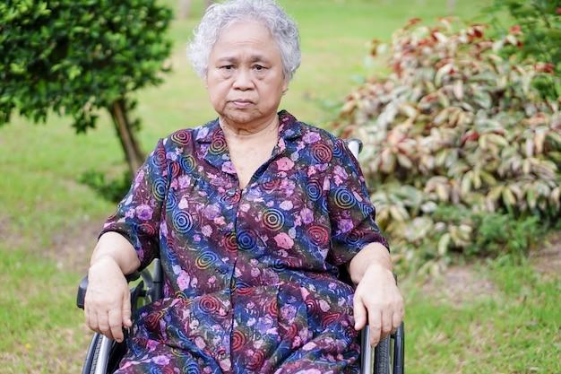 Il paziente luminoso del fronte di sorriso della donna anziana anziana o anziana anziana della signora su sedia a rotelle in parco. Foto Premium