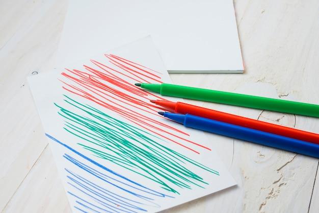 Il pennarello colorato e la carta con il colpo di penna sulla tavola di legno bianca Foto Gratuite
