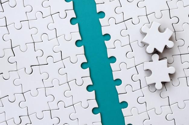 Il percorso blu è posto sulla piattaforma di un puzzle piegato bianco Foto Premium
