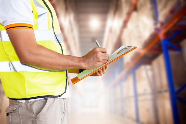 Il personale del magazzino è in possesso di un blocco per appunti con l'inventario dei prodotti in magazzino. Foto Premium