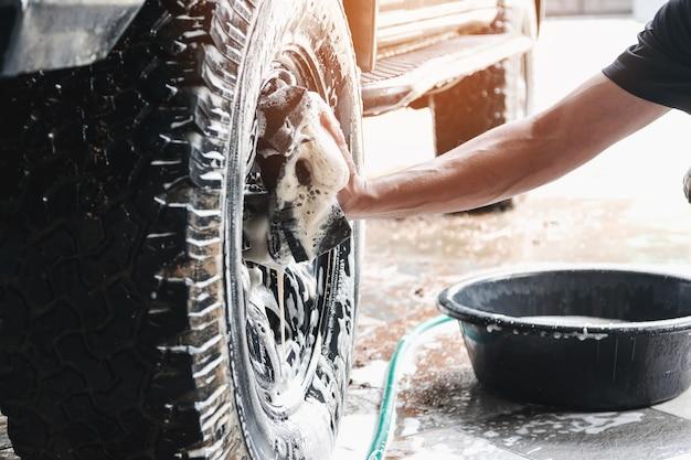 Il personale dell'autolavaggio sta usando una spugna inumidita con acqua e sapone per pulire le ruote dell'auto. Foto Premium