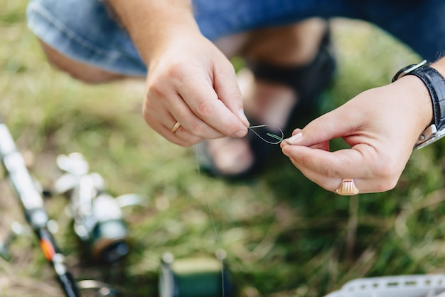 Il pescatore si prepara per la cattura delle carpe sul lago in estate Foto Premium