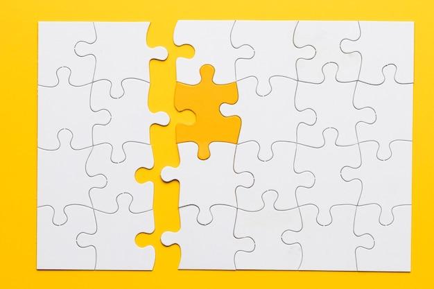 Il pezzo giallo si collega con pezzi di puzzle bianchi su sfondo chiaro Foto Gratuite