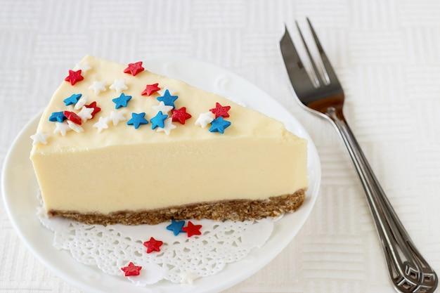 Il piatto bianco di cheesecake di new york della fetta è servito per la celebrazione il 4 luglio in usa Foto Premium