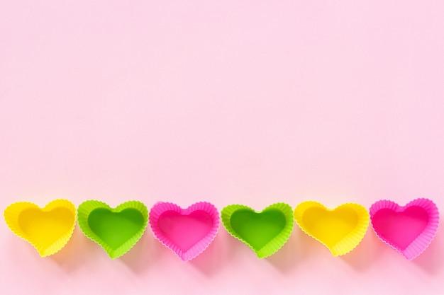 Il piatto colorato degli stampi a forma di cuore del silicone per i bigné bollenti ha allineato nel bordo inferiore di fila su fondo di carta rosa. Foto Premium